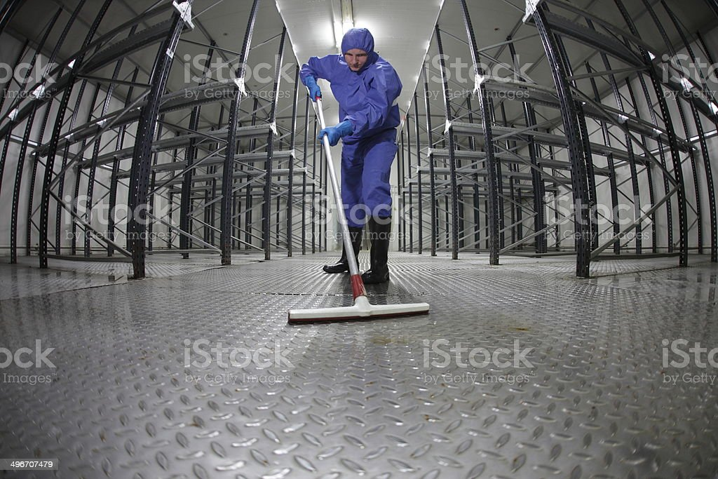 worker in protective uniform cleaning floor in empty storehouse stock photo