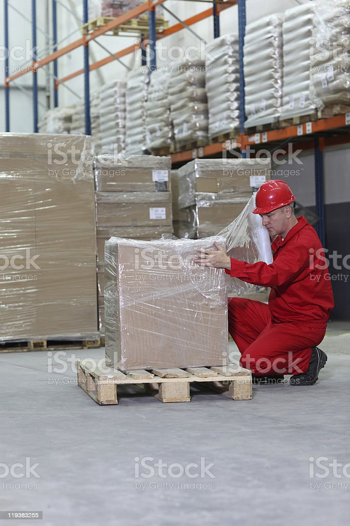 Worker in red Robin box on the wooden pallet in a warehouse stock photo