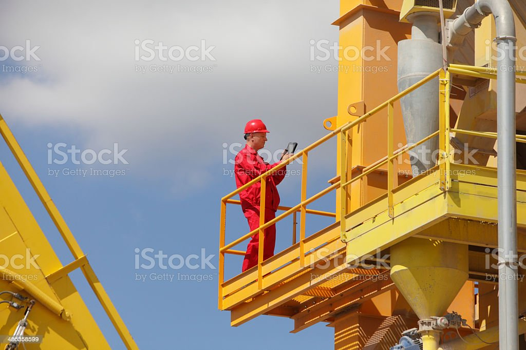 worker in red uniform with tablet on industrial platform stock photo