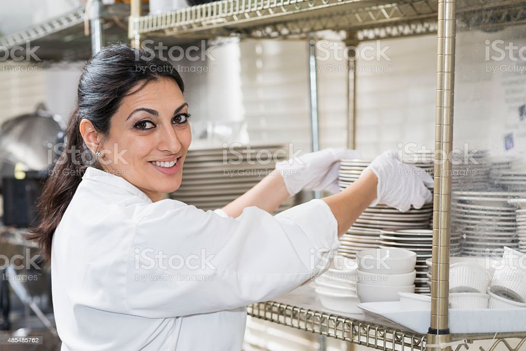 Worker in restaurant carrying stack of plates stock photo