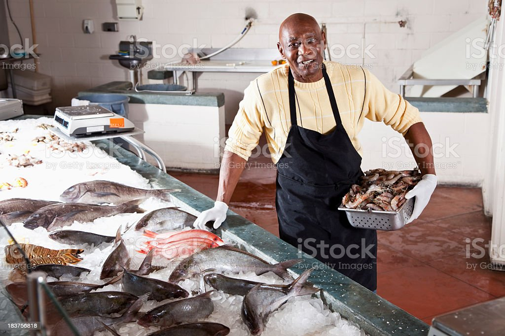Worker in seafood market by fresh fish display stock photo