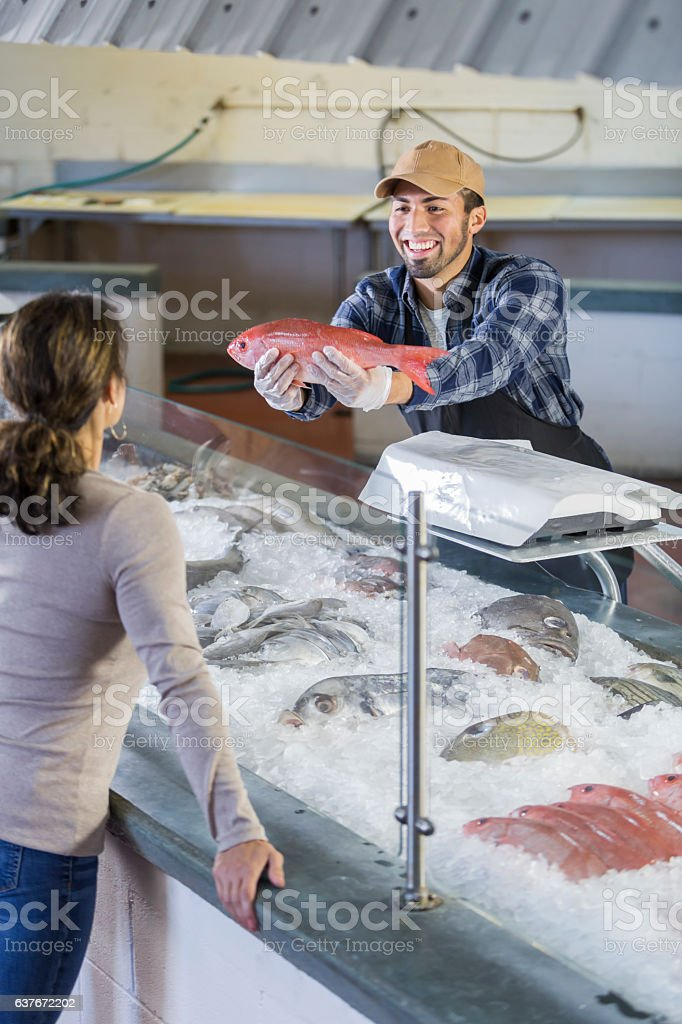 Worker in seafood market helping customer stock photo