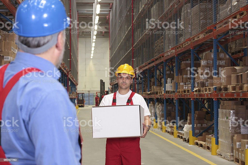 worker in uniform and hardhat carrying box royalty-free stock photo