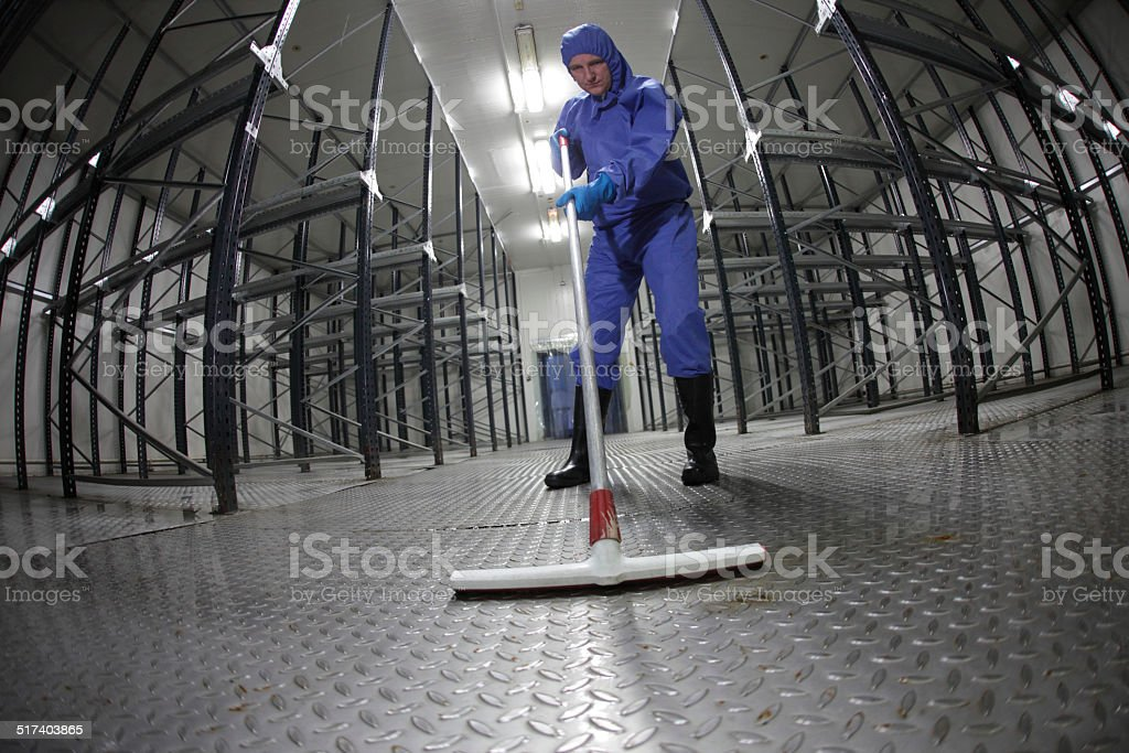 worker in uniform cleaning floor in empty storehouse stock photo