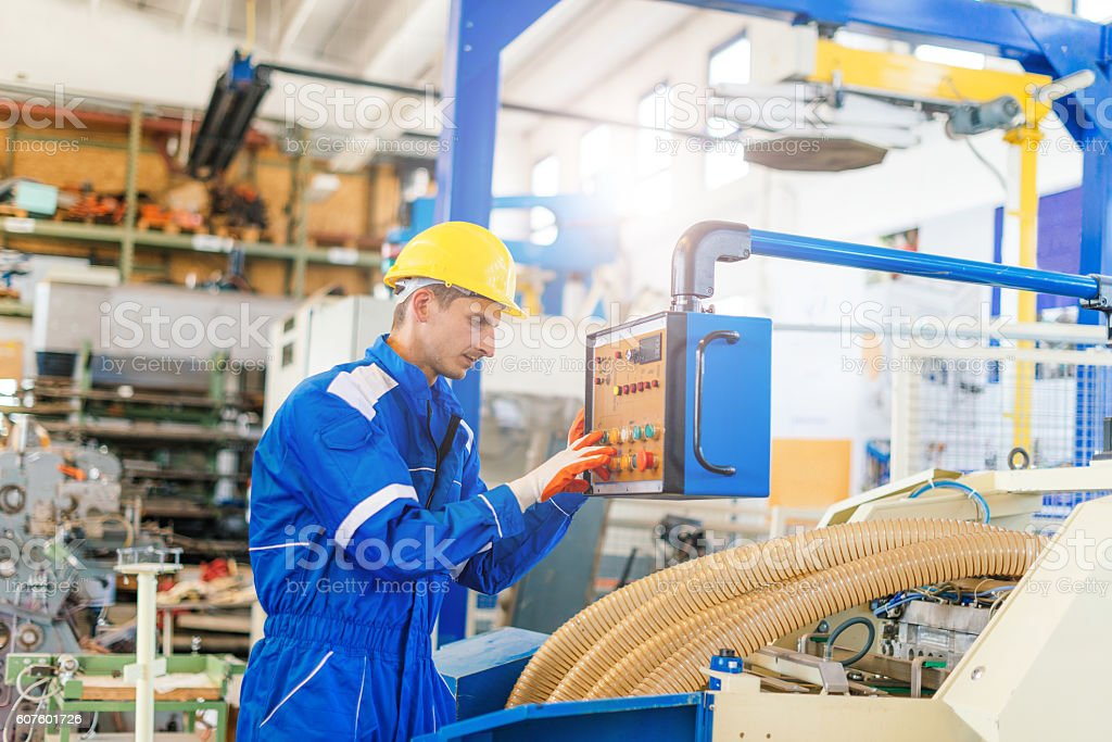 Worker in uniform starting the production process on machine stock photo