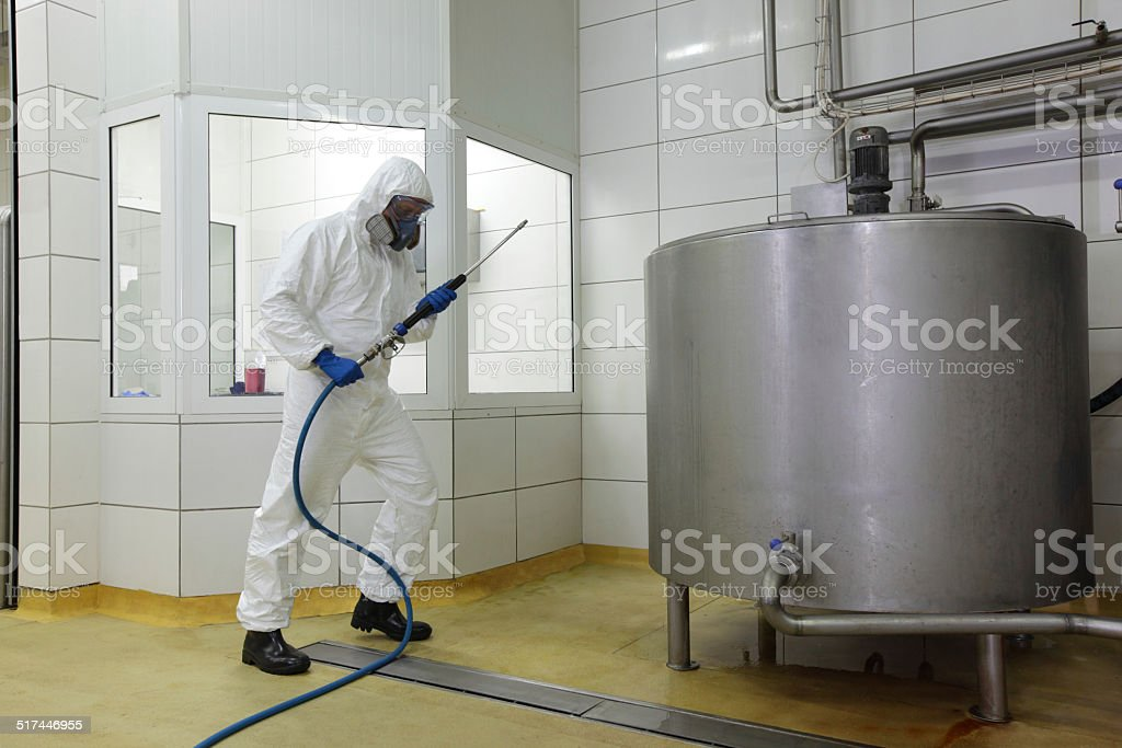 worker in uniform, with high pressure washer at plant stock photo