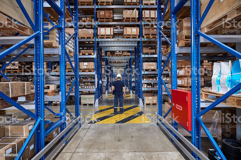 Worker in warehouse aisle stock photo
