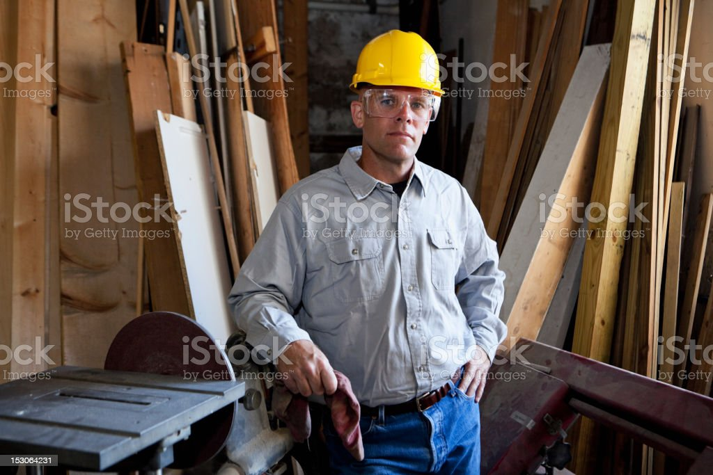 Worker in warehouse by lumber and table saw stock photo