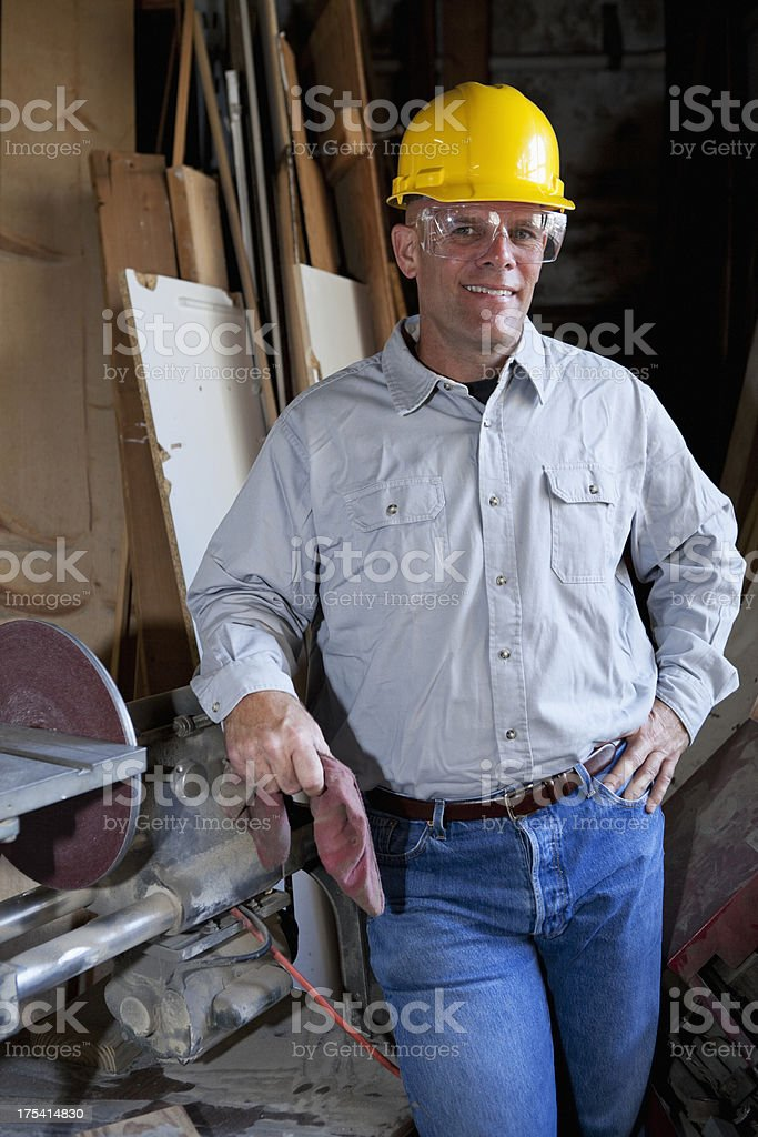 Worker in warehouse by lumber and table saw royalty-free stock photo