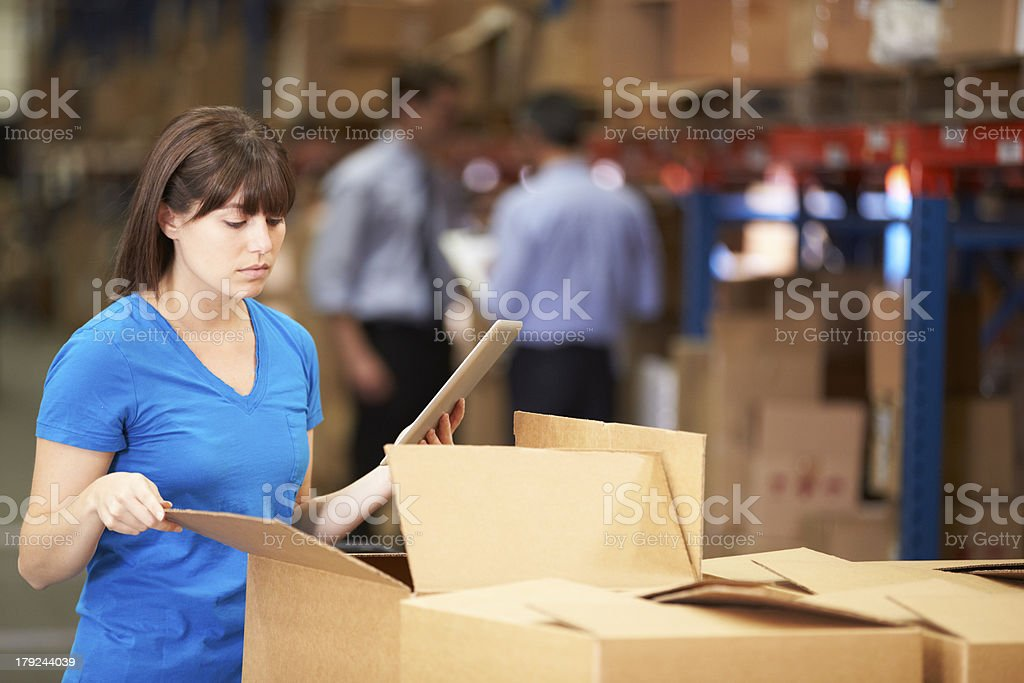 Worker In Warehouse Checking Boxes royalty-free stock photo