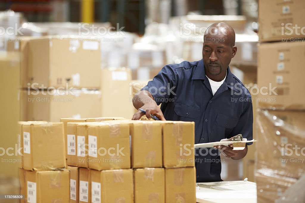 Worker In Warehouse Preparing Goods For Dispatch stock photo