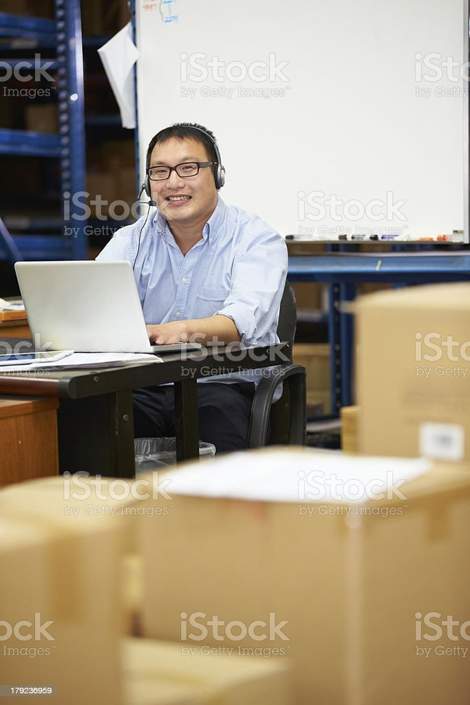 Worker In Warehouse Wearing Headset And Using Laptop royalty-free stock photo