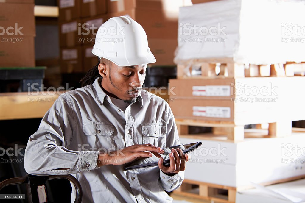 Worker in warehouse with digital tablet stock photo