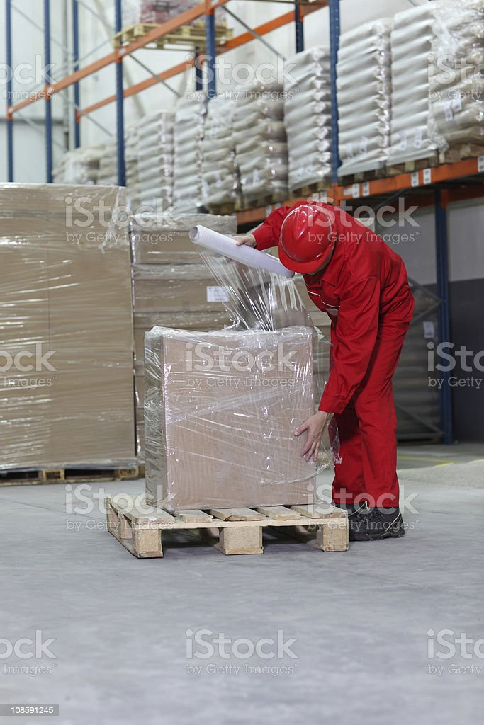 Worker in warehouse wrapping box in plastic wrap stock photo