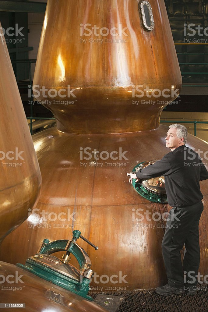 Worker in whisky distillery stock photo