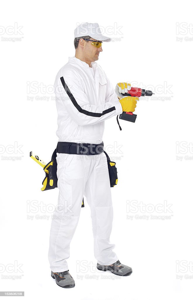 worker in white overalls drilling a hole stock photo