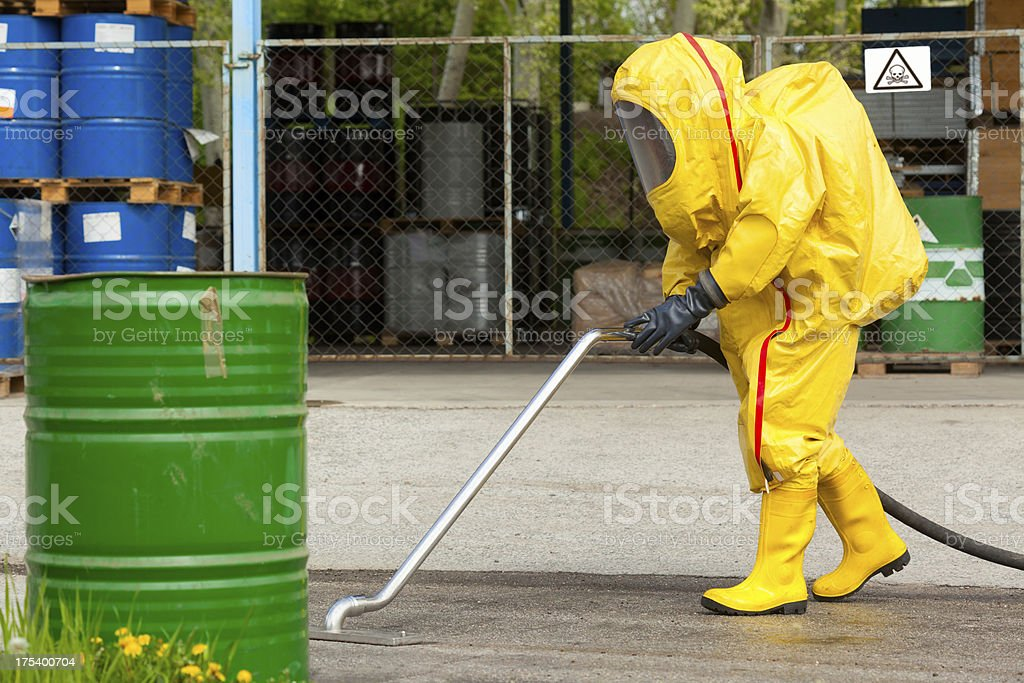 Worker in yellow hazmat suit cleaning ground stock photo