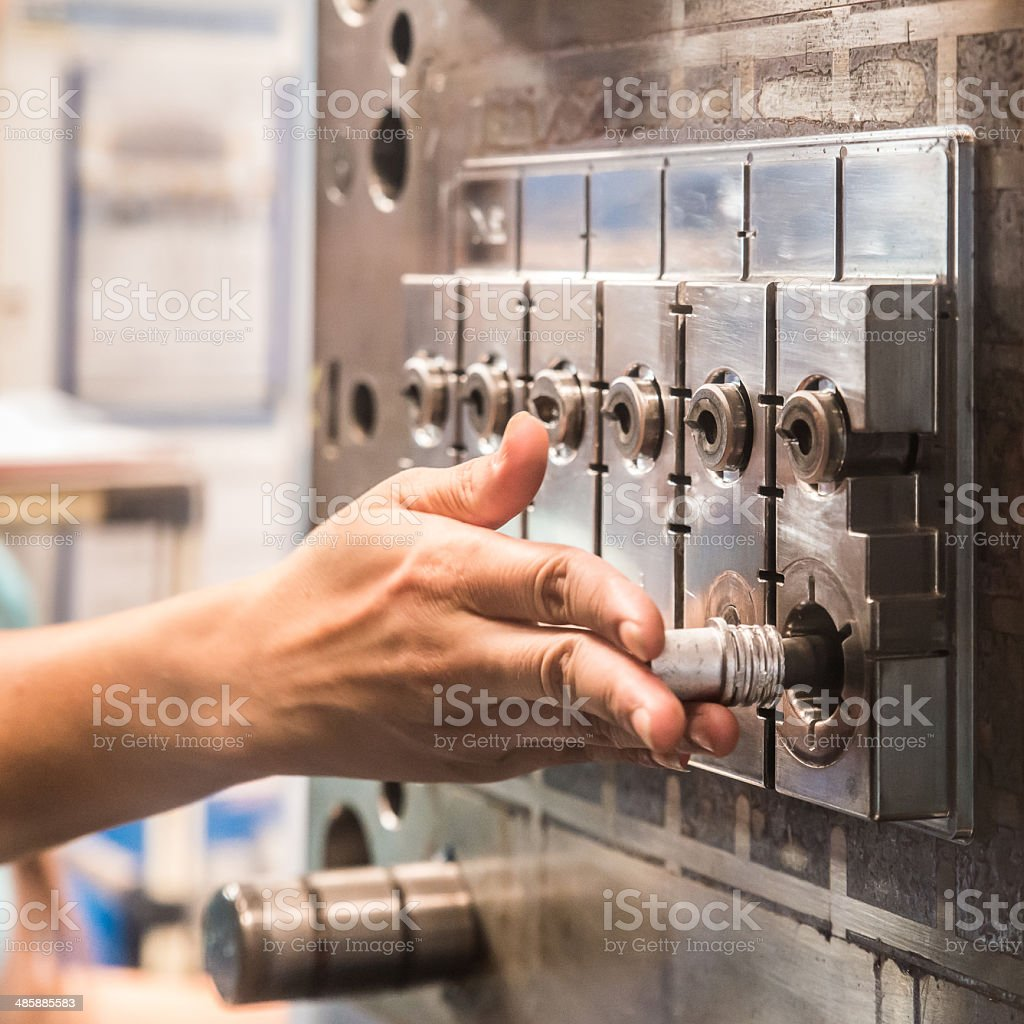 Worker insert spare parts in Injection molding machine stock photo