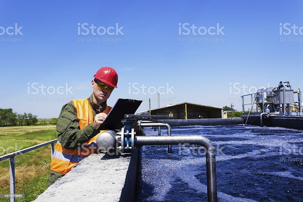 Worker inspecting valve stock photo