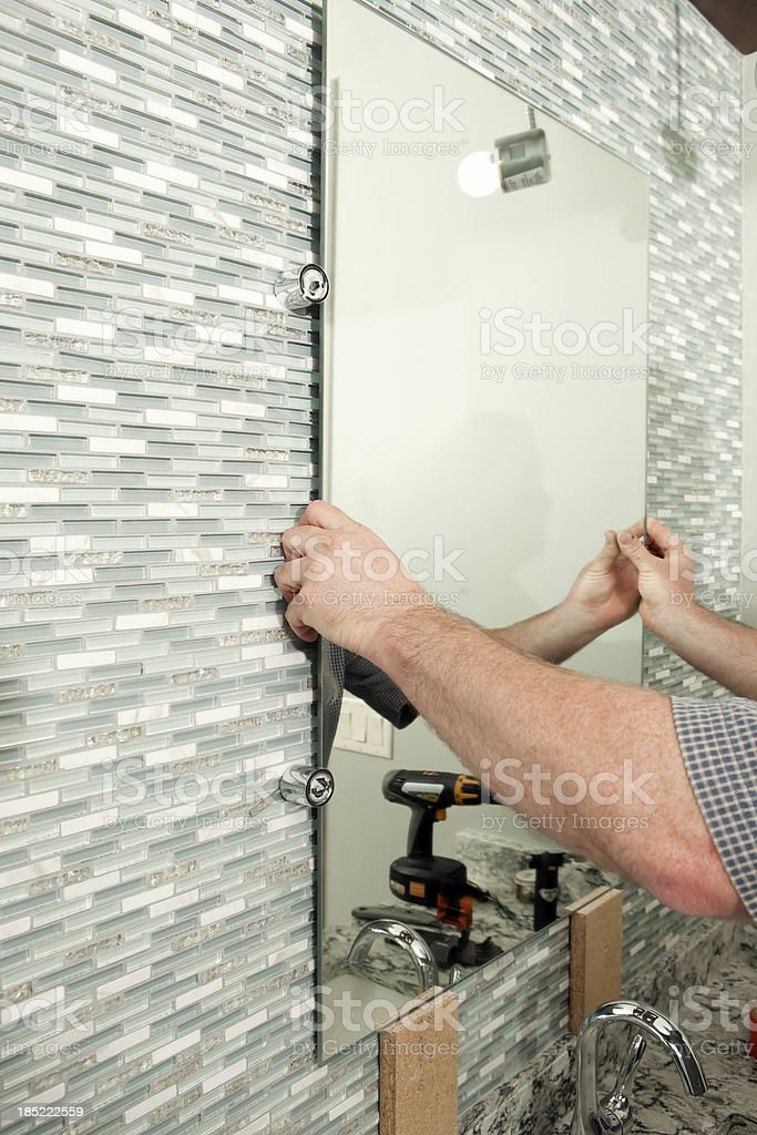 Worker Installing a New Bathroom Mirror stock photo