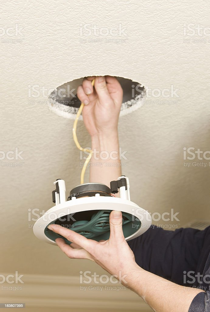 Worker Installing a Residential Ceiling Speaker stock photo