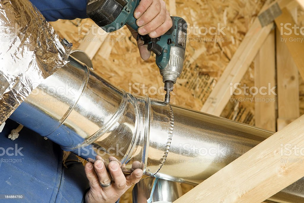 Worker Installing an Attic Vent Duct stock photo