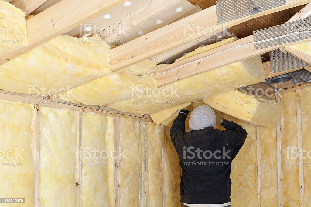 Worker Installing Fiberglass Batt Insulation between Roof Trusses stock photo