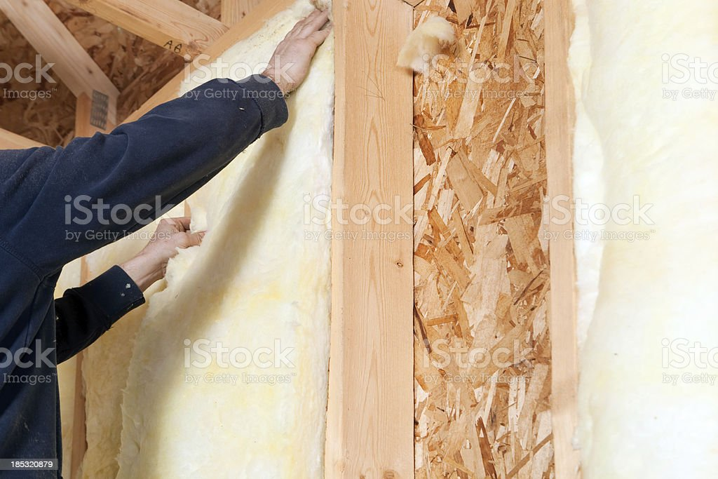 Worker Installing Fiberglass Batt Insulation between Wall Studs stock photo
