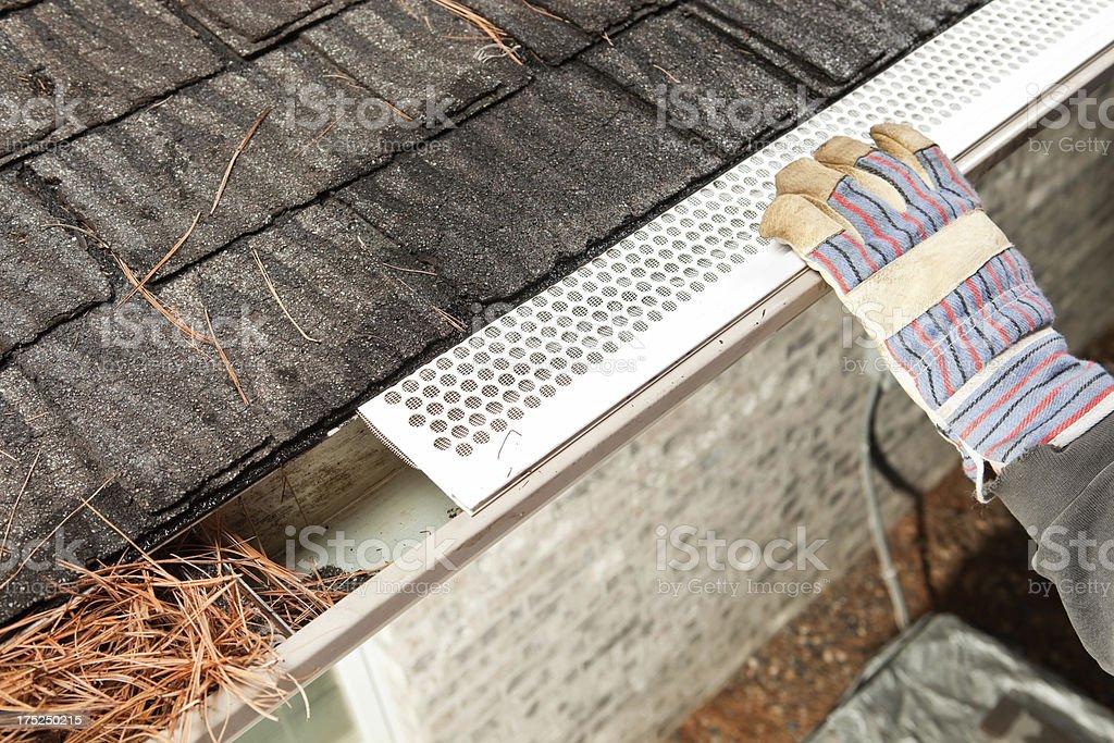Worker Installing Rain Gutter Guard Leaf Shield stock photo