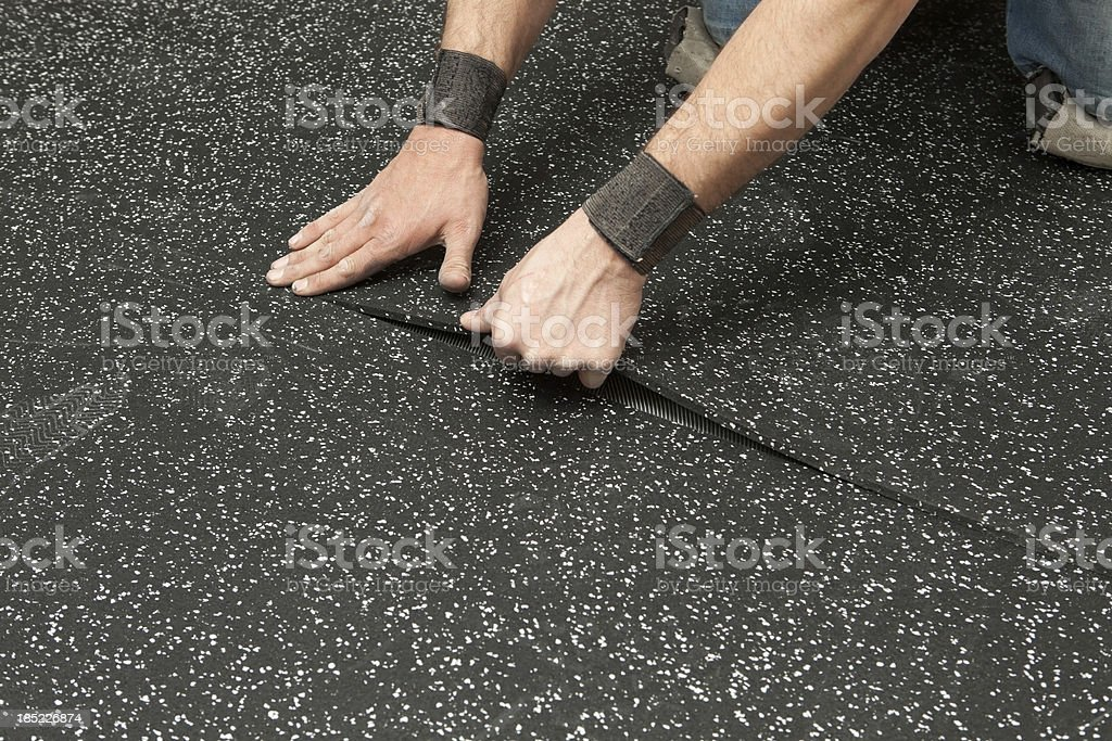 Worker Installing Recycled Rubber Floor stock photo