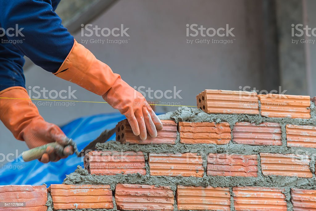 Worker installing red brick for construction site stock photo