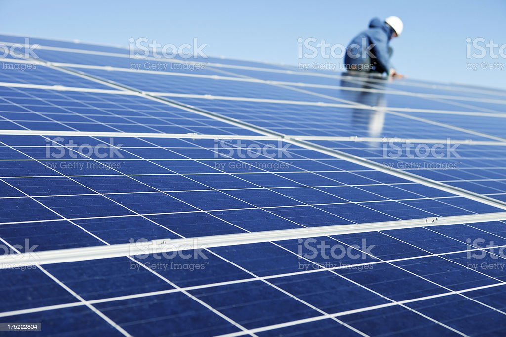 Worker Installing Rooftop Solar Panels stock photo