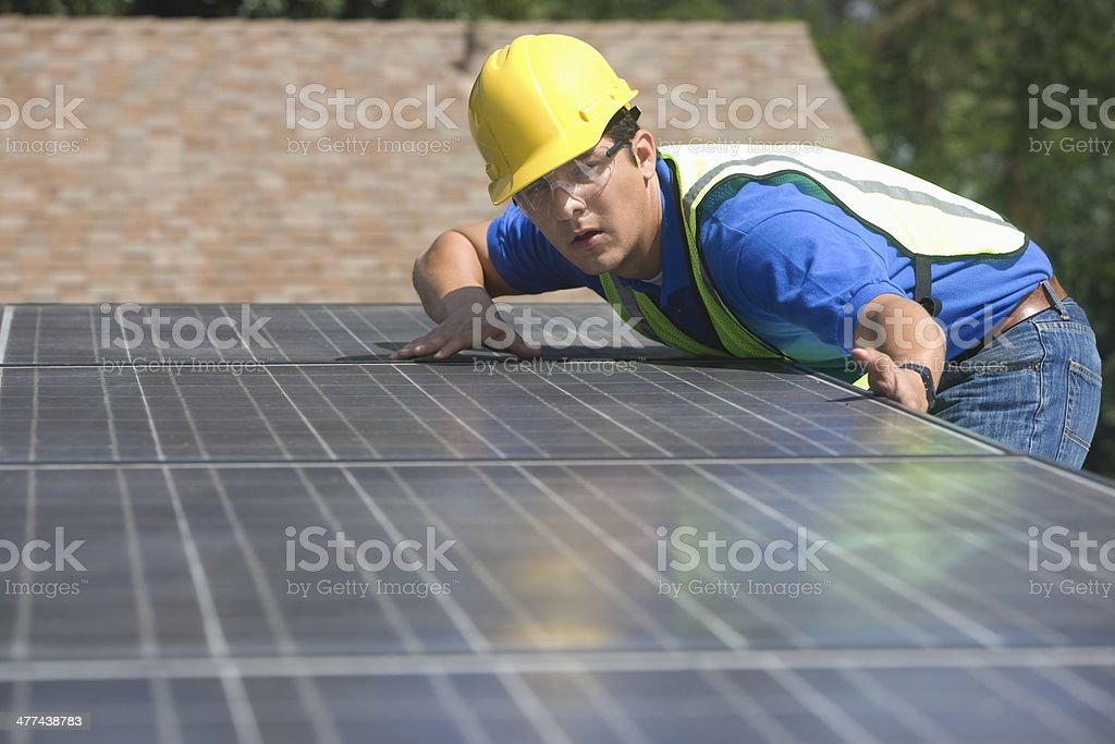 Worker Installing Solar Panels On Rooftop stock photo