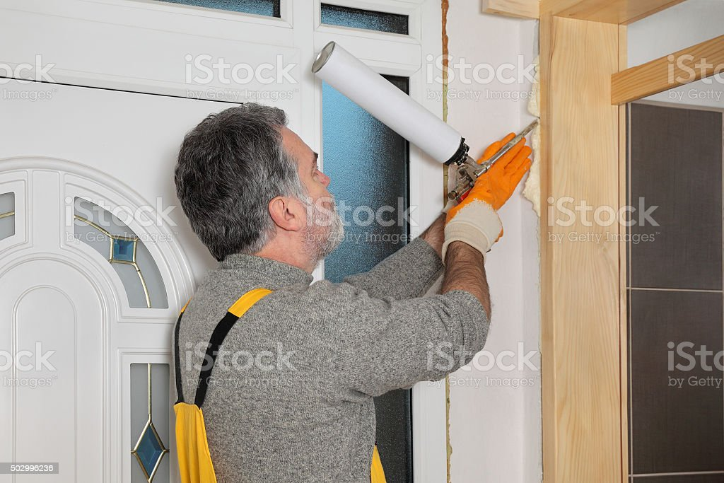 Worker installing wooden door, using polyurethane foam stock photo