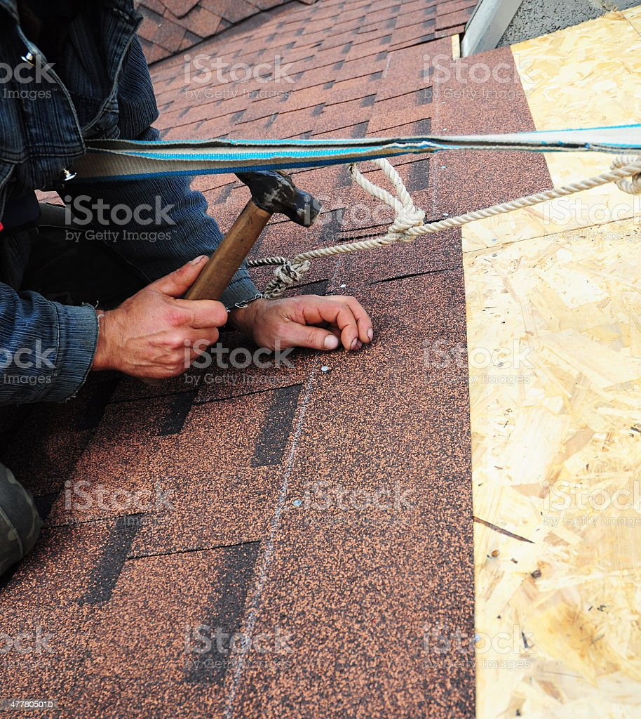 Worker installs bitumen roof shingles with safety  equipment stock photo