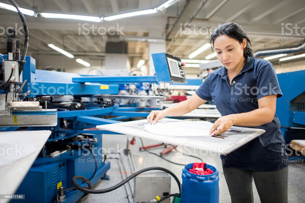 Worker ironing at a clothing factory stock photo
