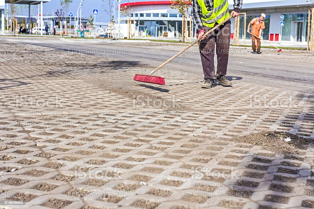 Worker is cleaning new parking place with red broom stock photo