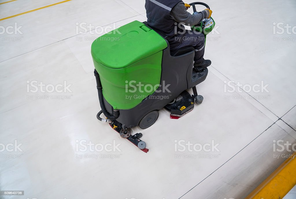 Worker is cleaning the floor with machine stock photo