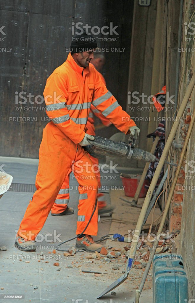 worker is drilling wall outdoor in Padua, Italy stock photo