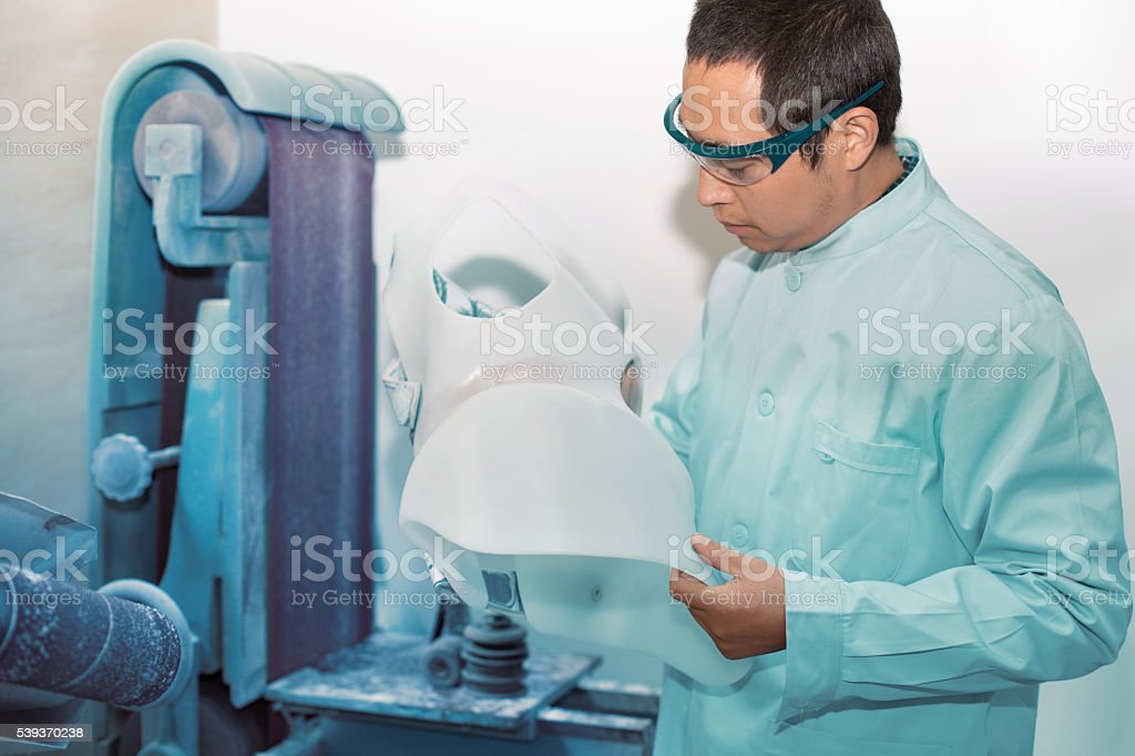 worker is using a drilling machine to process a prosthetic stock photo