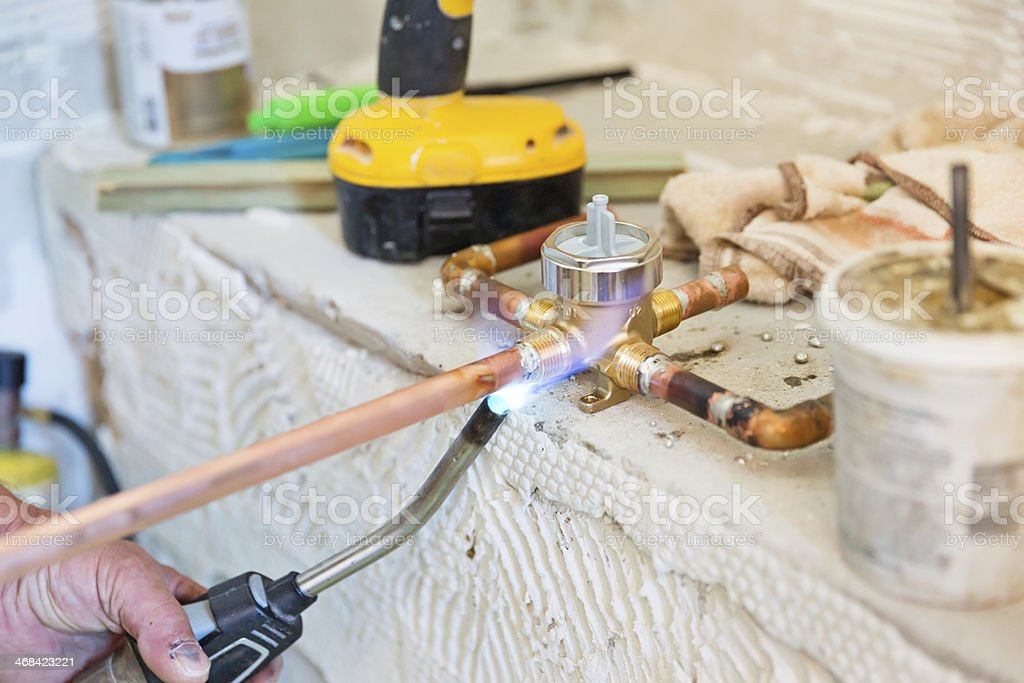 A worker is welding copper piping to a fitting. royalty-free stock photo