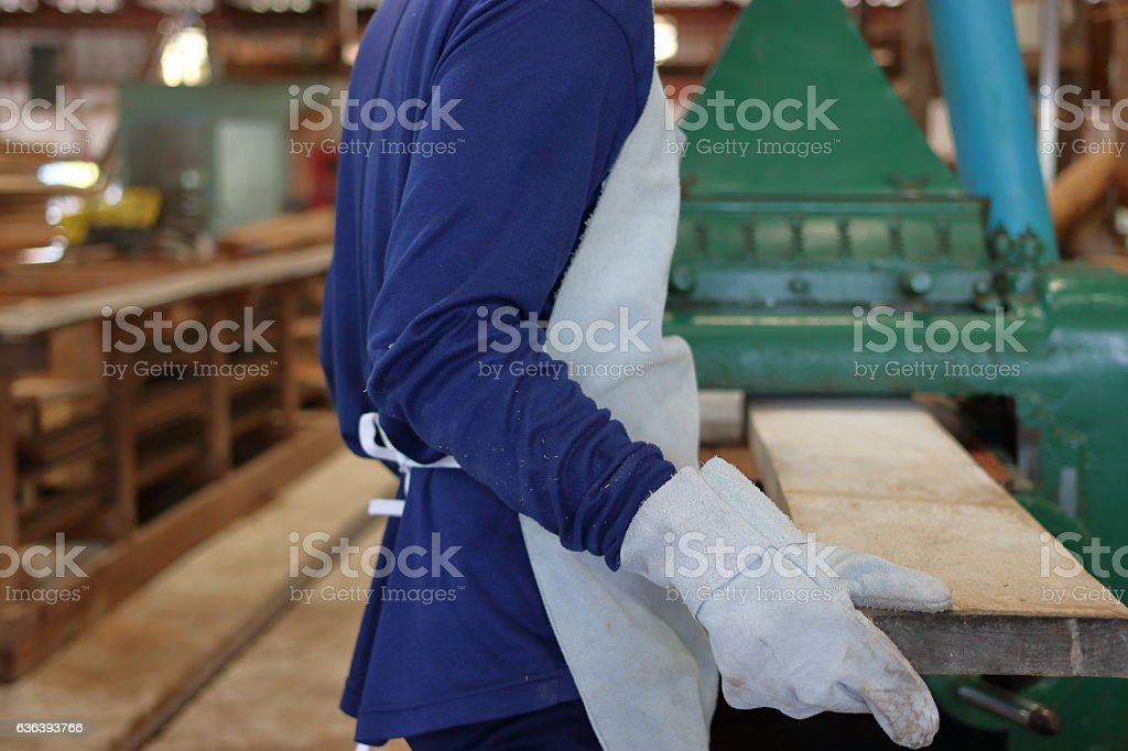Worker is working with planing of wood machine. stock photo