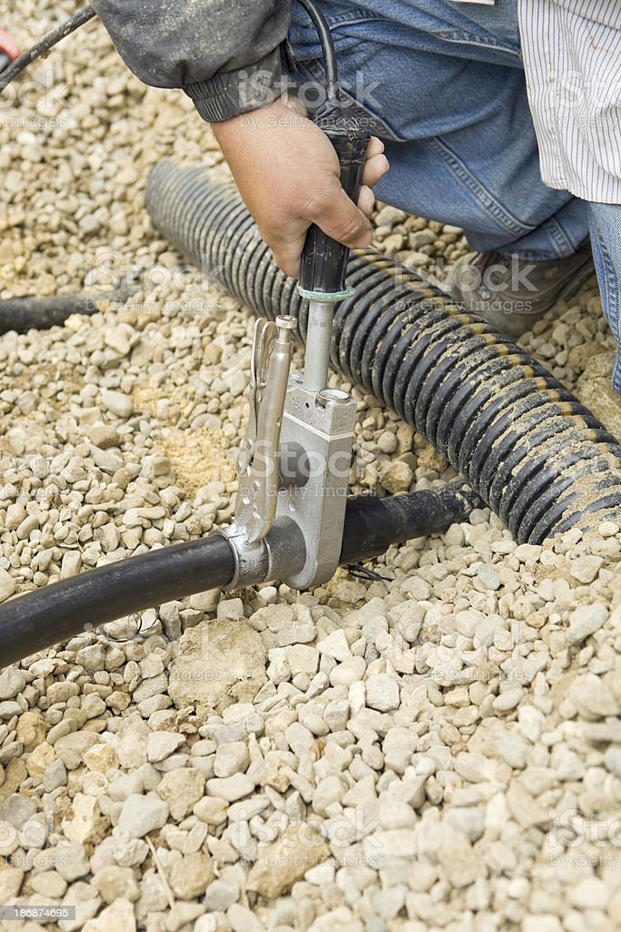 Worker Joining Residential Geothermal Heating/Cooling Pipe royalty-free stock photo