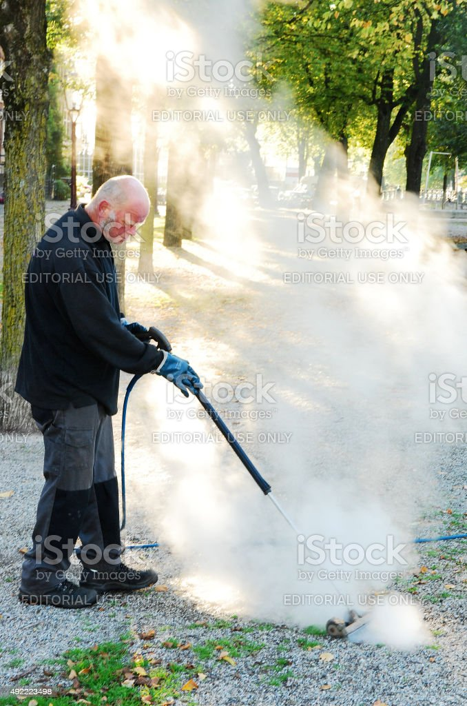 Worker killing weed using hot water stock photo