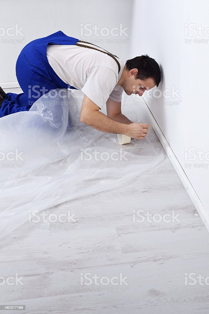 Worker laying protection film before painting stock photo