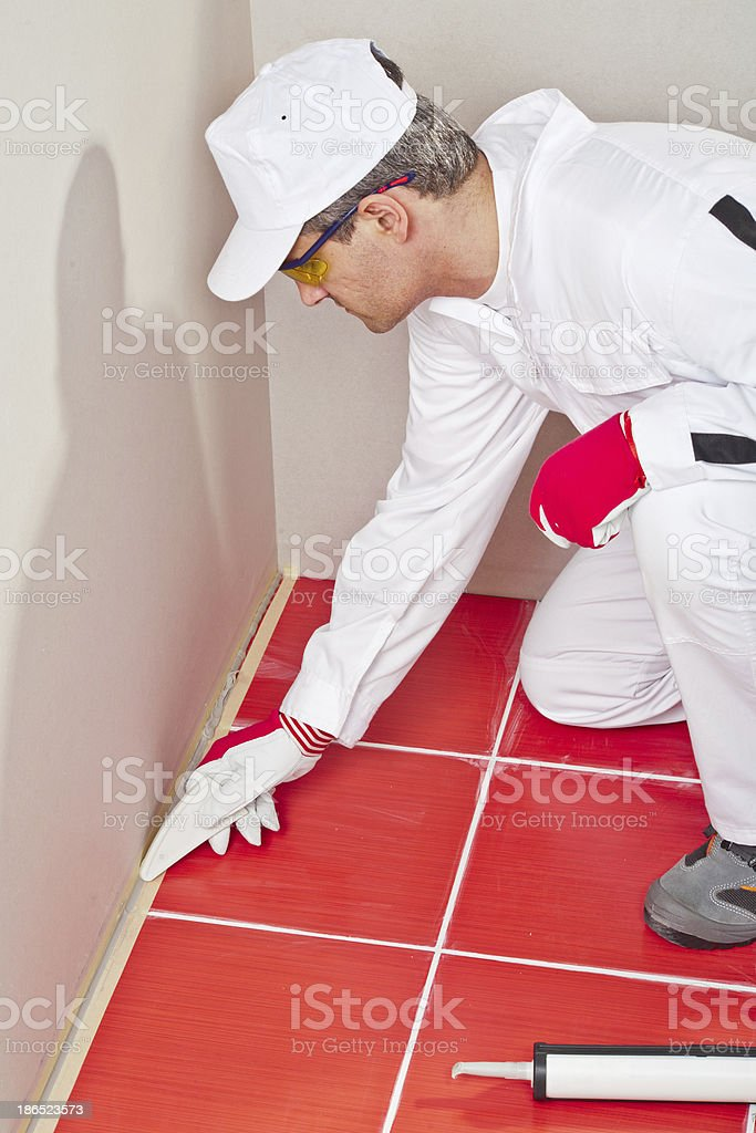 worker lays silicone sealant corner wall floor stock photo