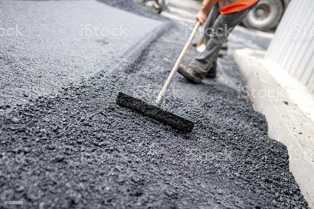 Worker levelling fresh asphalt on a road construction site stock photo
