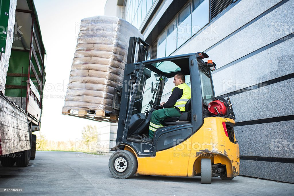 Worker loading pallet with a forklift into a truck. stock photo