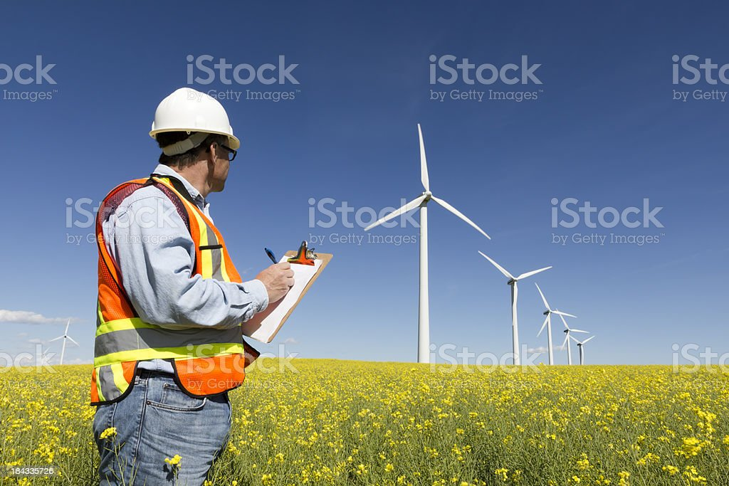 Worker looking at a field of wind turbines stock photo
