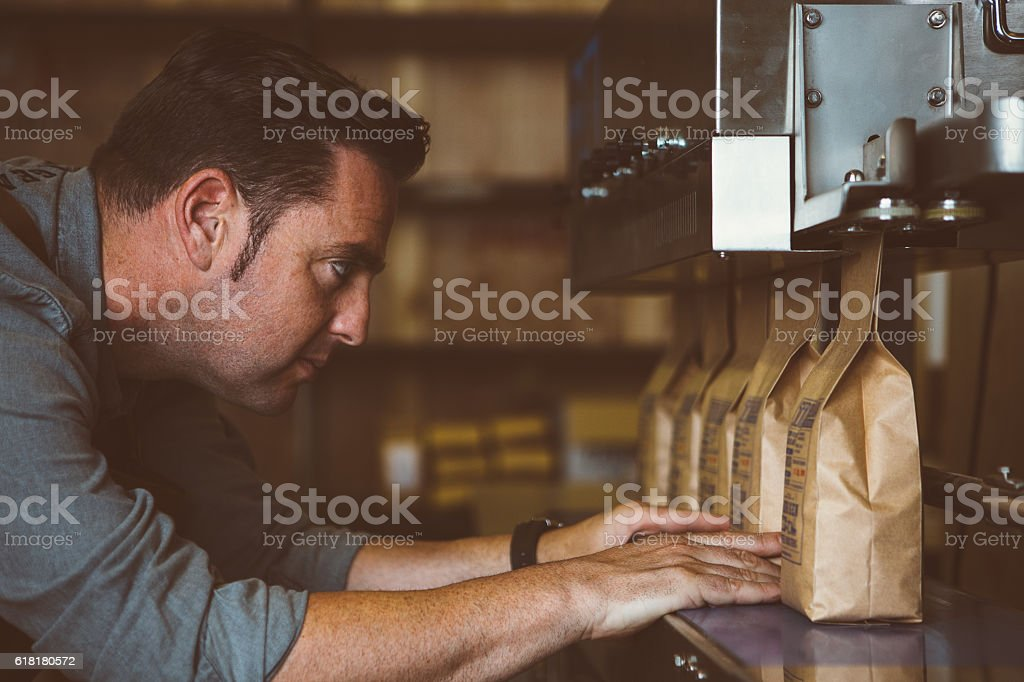 Worker looking at line of packed coffee beans stock photo